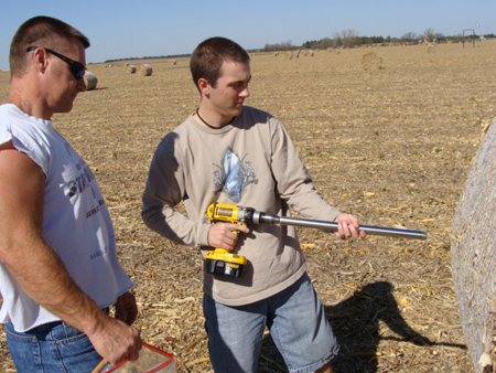 Greg Teichmeier and Dan Hatch prepare to draw a bale sample for analysis of moisture and carbon content in a biomass removal study at the Carbon Sequestration field sites.