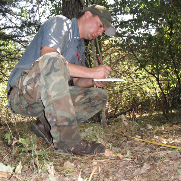 PhD student Kent Fricke documents understory vegetation before invasive trees and shrubs are removed.